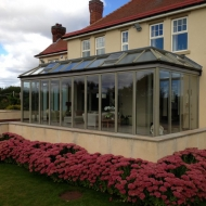 This stunning orangery combines a lean-to glass roof with 3 sets of SUNFLEX bifold doors including a 10-panel, centre-opening set