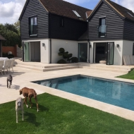 This stylish new-build home features bifold doors on the ground floor that connect the kitchen and living room with the stylish patio and swimming pool
